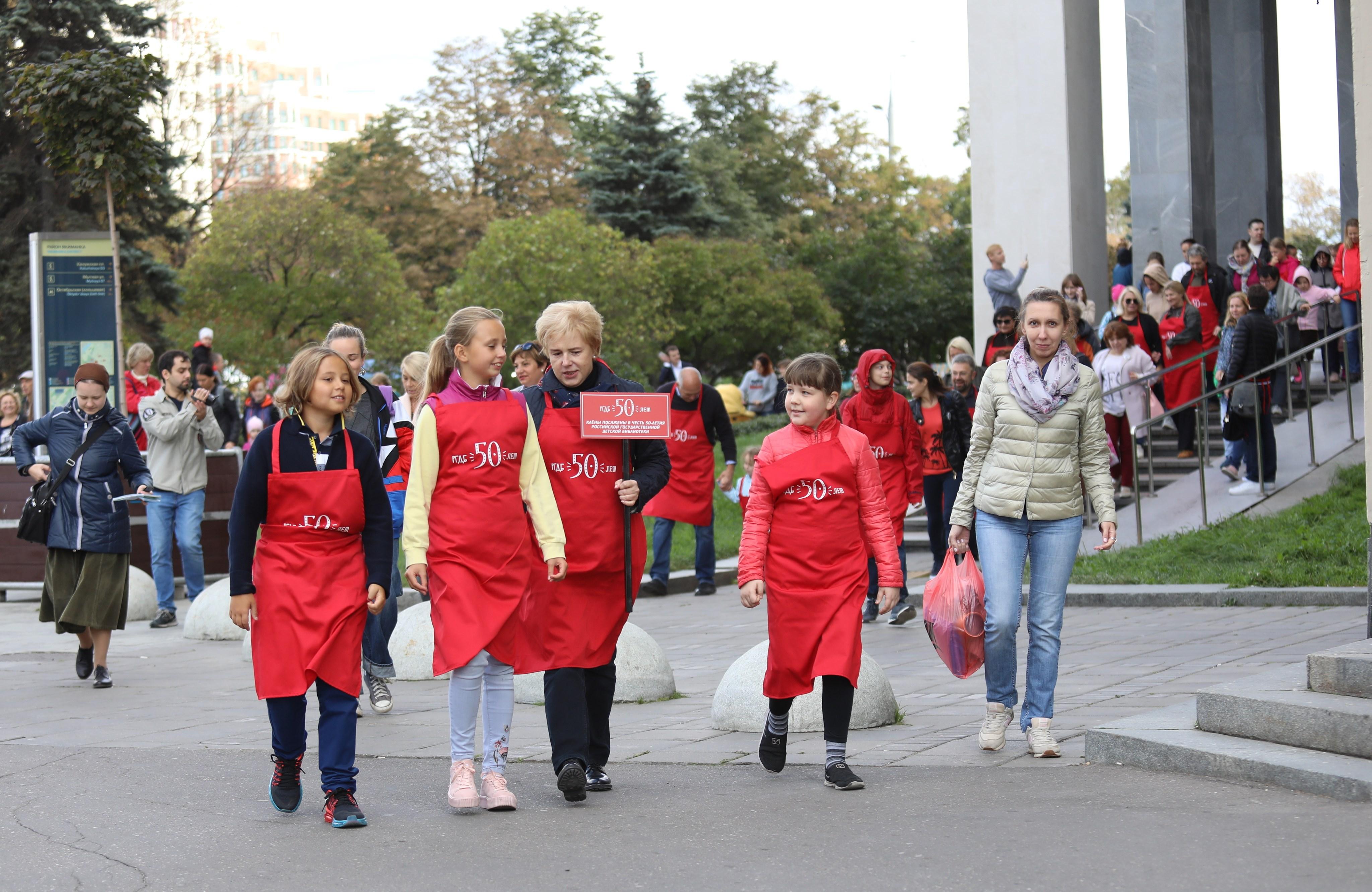 Директор библиотеки Мария Веденяпина (с табличкой) ведет гостей праздника сажать клены / Пресс-служба РГДБ