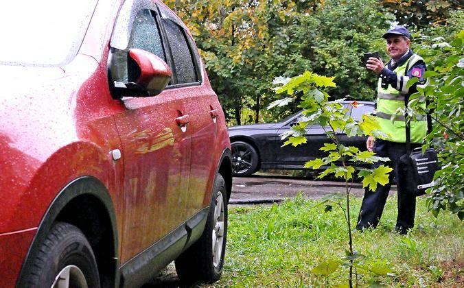 Инспектор МАДИ Алексей Прохоров фиксирует нарушение правил парковки автомобиля на планшет с установленной специальной программой / Светлана Колоскова, «Вечерняя Москва»