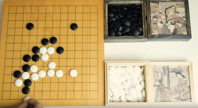 Го — это китайская настольная игра посложнее шахмат. В ней задействованы два игрока, один из которых получает черные камни, другой — белые / скриншот видео на youtube-канале «ДА НИЛ»