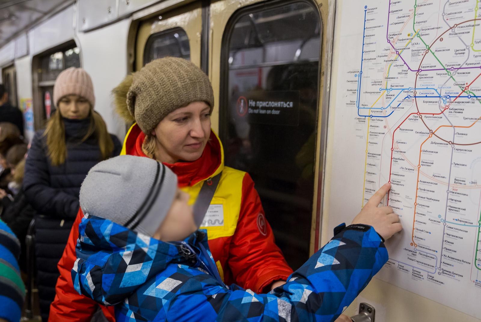 Сотрудница Центра обеспечения мобильности пассажиров Московского метрополитена помогает юному москвичу доехать до нужной станции