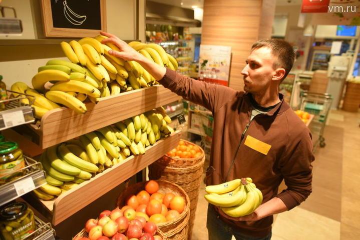 """Продавец сетевого магазина Борис Акимов раскладывает только что привезенные бананы на деревянные стеллажи. Проблем, по его признанию и по уверению его коллег, с поставками продовольствия нет. Ретейлеры получают партии продуктов питания ежедневно / Александр Кожохин, """"Вечерняя Москва"""""""